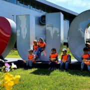 """Przedszkolaki poznają okolice UG, na zdjęciu grupa dzieci siedzi na napisie """"I love UG"""""""